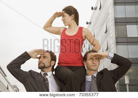 Hispanic businesswoman sitting on co-worker's shoulders
