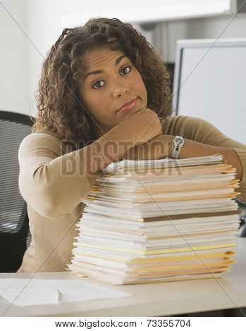 African businesswoman leaning on stack of paperwork