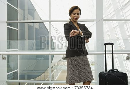 Hispanic businesswoman checking watch