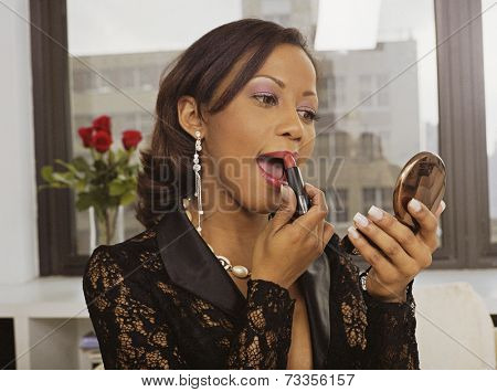 Hispanic woman applying lipstick