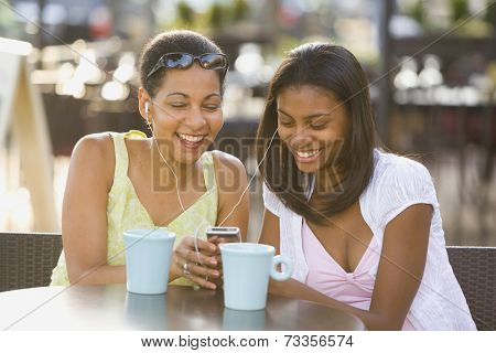 African mother and daughter listening to mp3 player