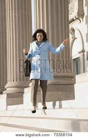 Hispanic businesswoman walking down steps