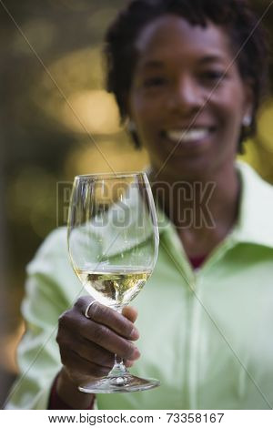 African woman holding up wine glass