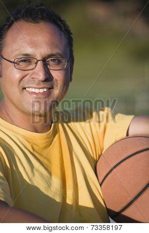 Hispanic man holding basketball