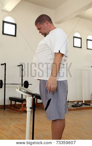 man with overweight standing on scales in the gym