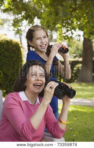 Hispanic grandmother and granddaughter looking through binoculars