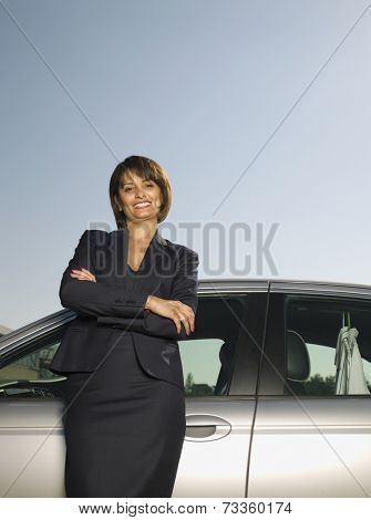 Indian businesswoman leaning on car
