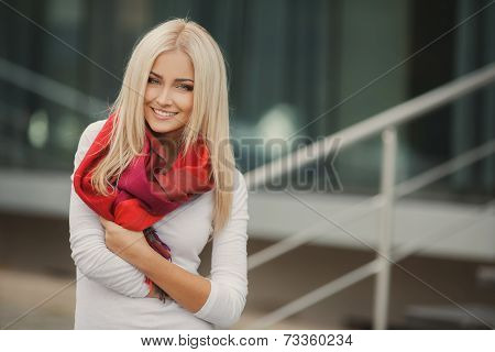 Portrait of young blonde beautiful woman in warm autumn scarf in the street.
