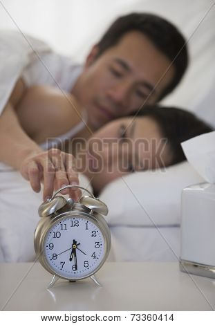 Asian man touching alarm clock
