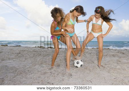 Multi-ethnic girls playing soccer at beach