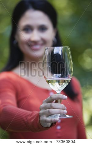 Hispanic woman holding up wine glass