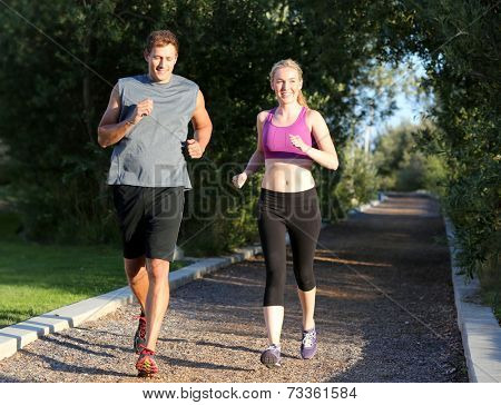 Happy couple running on a trail outside