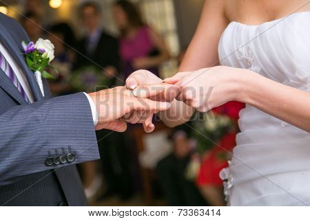 Bride Putting A Wedding Ring On Groom's Finger