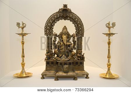 A metal statue of ganesha with musical instruments