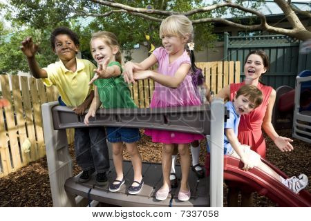 Preschool children playing on playground with teacher