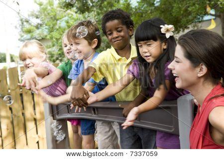 Crianças pré-escolares, brincar no parque infantil com professor