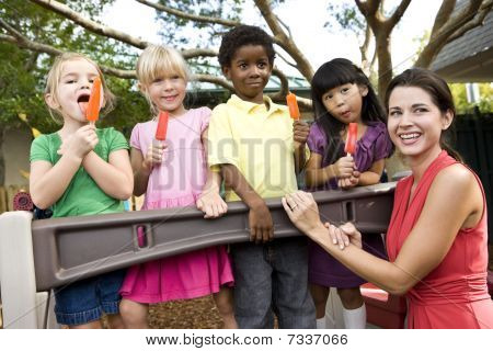 Preschool children on playground with teacher eating popsicles