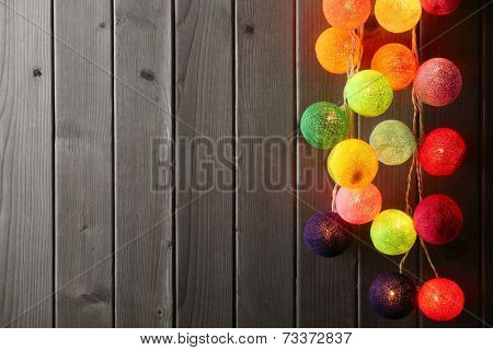 Christmas ball lights over wood plank.