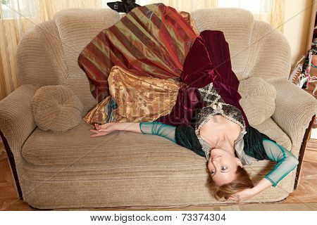 Actress in a medieval dress lying upside down on the sofa arms outstretched