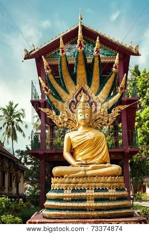Statue Of Meditating Buddha In Traditional Theravada Style. Asian City Religious Architecture At Pub