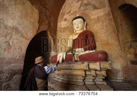 Bagan, Myanmar - 14 Jan, 2014: Unidentified Burmese Man Brings Religious Offerings To Buddha Statue