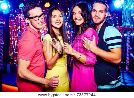 Portrait of two couples clubbing at night