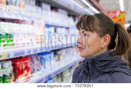 Samara, Russia - October 5, 2014: Young Woman Choosing Fresh Milk Produces At Shopping In Dairy Supe