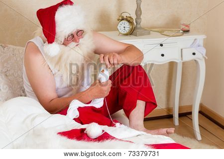 Funny Santa Claus mending his own socks