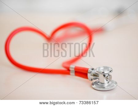Red medical stethoscope in shape of heart