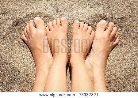 Feet of mother with daughter relaxing and sunbathing on a beach