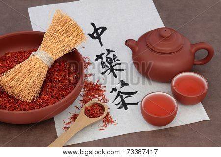 Safflower herb tea with terracotta teapot and cups and calligraphy script on rice paper. Translation reads as chinese herbal tea.