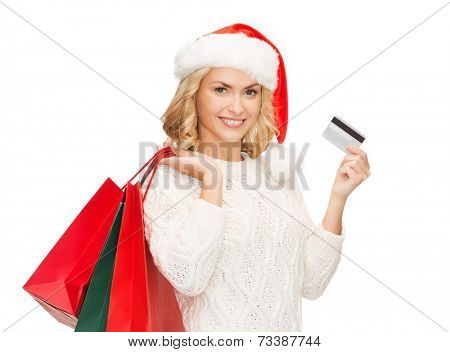 sale, gifts, christmas, xmas concept - smiling woman in santa helper hat with shopping bags and credit card