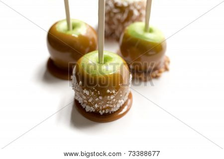 Green caramel apples on white