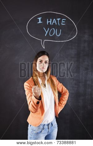 Woman next to a chalkboard with the words I hate you
