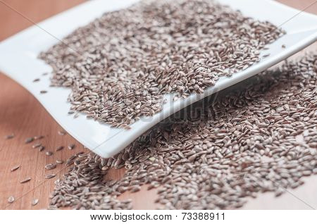 White ceramic bowl full of hemp seeds over old wood background