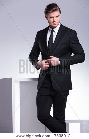 Young business man looking at the camera while closing his jacket. On grey studion background.