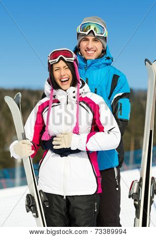 Half-length portrait of two hugging alps skiers with skis in hands
