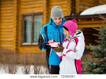 Half-length portrait of man giving present to woman outdoors during winter vacations