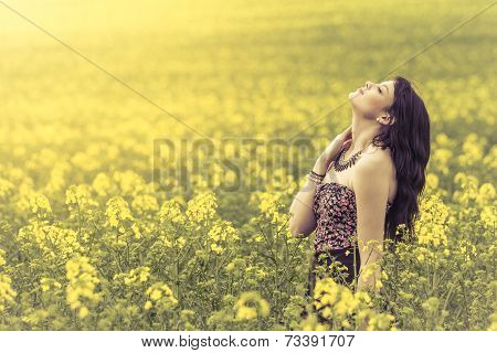 Beautiful Woman In Meadow Of Yellow Flowers With Head Up