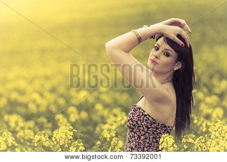 Beautiful Woman In Meadow Of Yellow Flowers With Hands Up