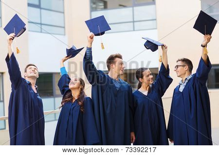education, graduation and people concept - group of smiling students in gowns waving mortarboards outdoors
