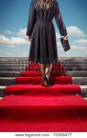 Elegant woman in black coat climbing a red carpet stairway