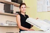 stock photo of secretary  - Pretty young secretary using a copy machine - JPG