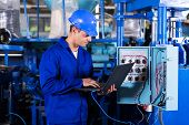 stock photo of status  - industrial programmer checking control box status with laptop computer - JPG