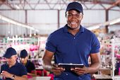 stock photo of clipboard  - handsome african american textile worker holding a clipboard - JPG