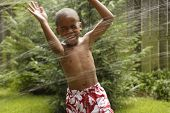 stock photo of sprinkler  - African American boy playing in sprinkler - JPG