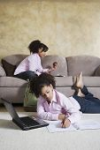 stock photo of identical twin girls  - African twin sisters doing homework - JPG