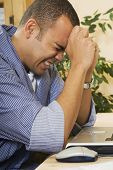 image of pacific islander ethnicity  - Frustrated Pacific Islander man next to laptop - JPG