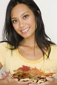 stock photo of pacific islander ethnicity  - Pacific Islander woman holding autumn leaves - JPG