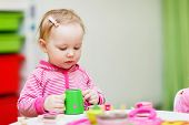 pic of daycare  - Adorable toddler girl playing with toys at home or daycare place - JPG